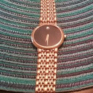 Movado black face with diamond goldtone strap